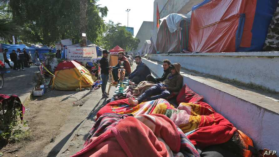Iraqi anti-government protesters are pictured where they sleep on the side of a road in the Iraqi capital Baghdad's Tahrir…