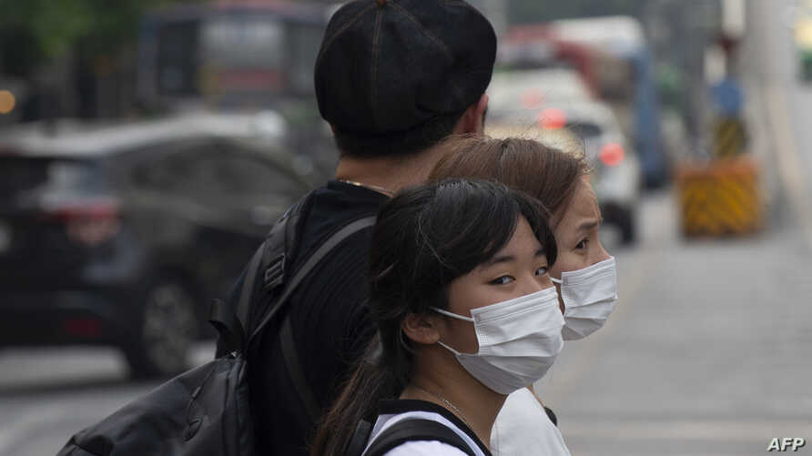 People wear face masks as haze continue to blanket Thailand's capital in Bangkok on January 20, 2020. (Photo by Romeo GACAD /…