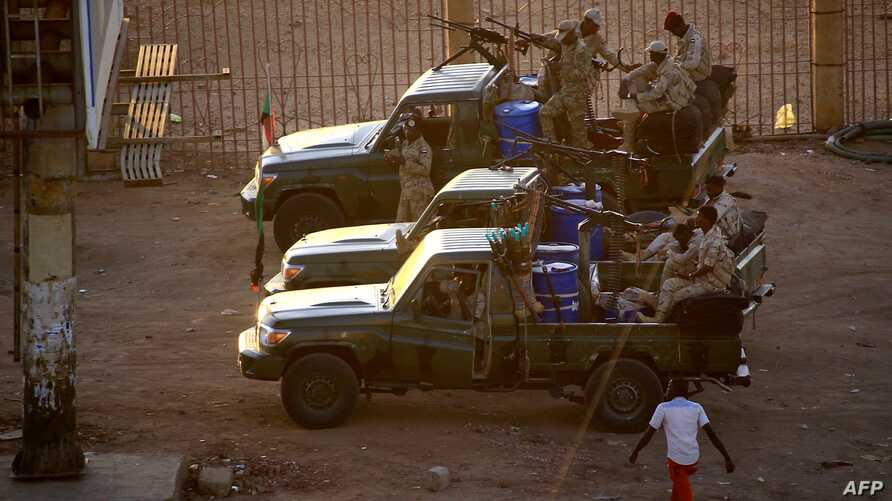 Members of Sudan's intelligence services shoot bullets in the air at the headquarters of the Directorate of General…