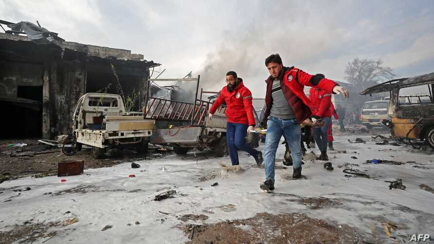 Syrian paramedics carry away on a stretcher a wounded man following a regime air strike on a vegetable market in Syria's last…