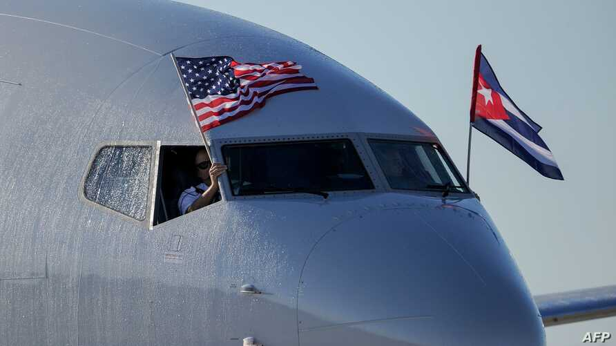 (FILES) In this file photo taken on November 28, 2016, an American Airlines plane fluttering US and Cuba national flags arrives…