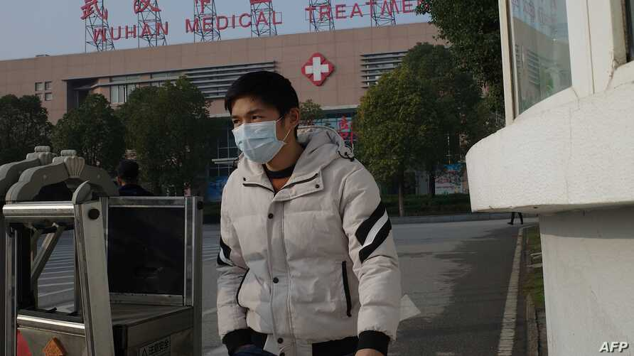 A man leaves the Wuhan Medical Treatment Centre, where a man who died from a respiratory illness was confined, in the city of…