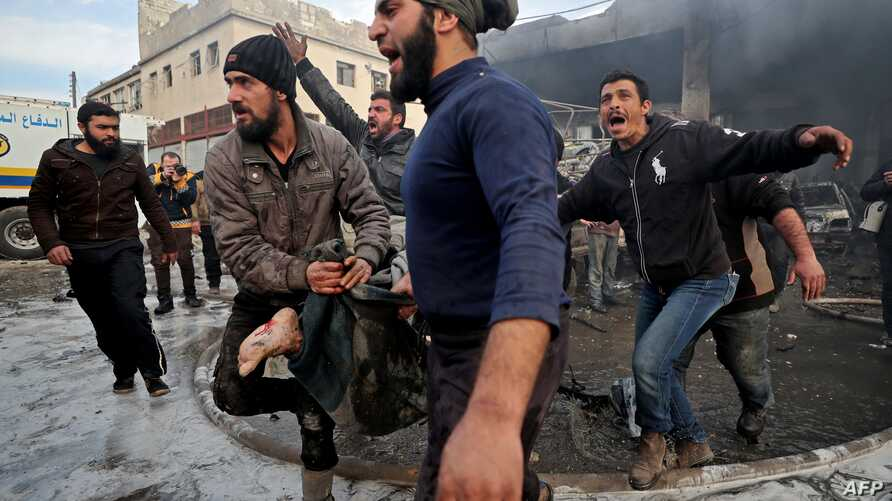 Syrians carry away the body of a man retrieved from the rubble of a building following a regime air strike on a vegetable…