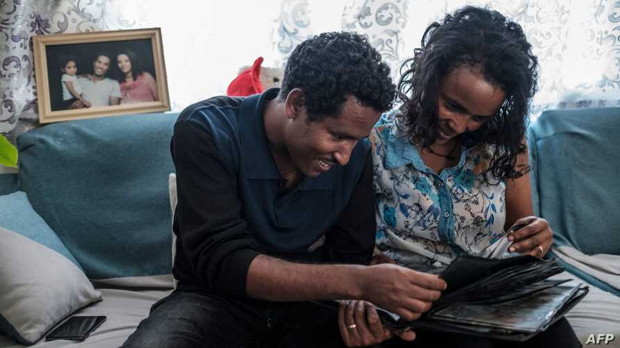Getahun Fetana (L) and his wife Emebet Melaku (R) looks at photographs in a family album in their home in the city of Gondar,…
