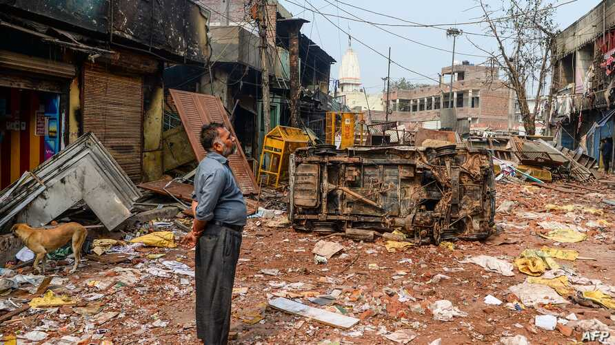 TOPSHOT - A resident look at burnt-out and damaged residential premises and shops following clashes between people supporting…