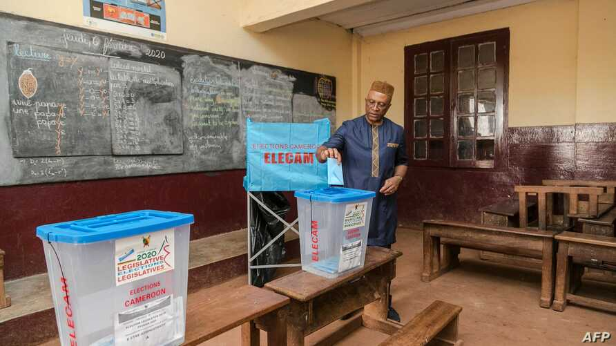 The Governor of the Central Region of Cameroon, Paul Naseri Bea, casts his ballot in the general and municipal elections in…