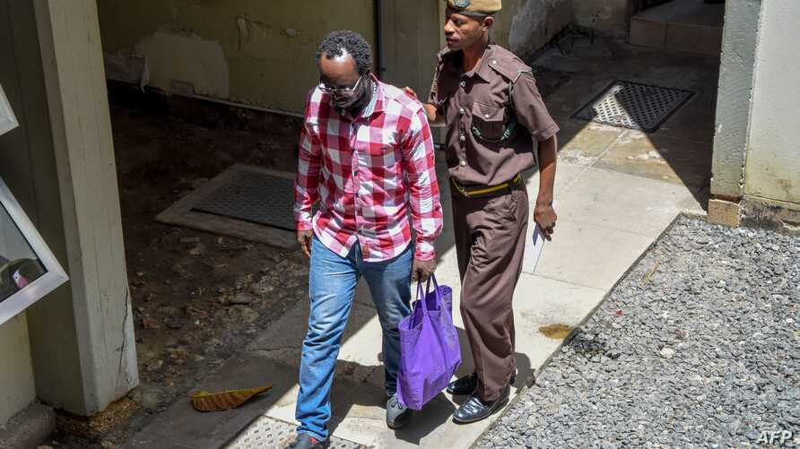 Tanzanian journalist Erick Kabendera (L) leaves the prison where he had been held for several months on February 24, 2019 in…