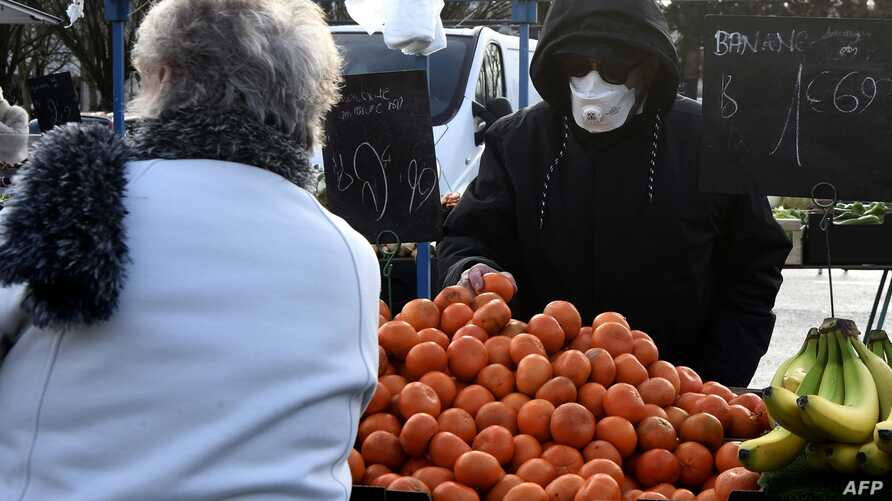 TOPSHOT - A man wearing a protective mask shops in the market of Crepy-in-Valois on March 1, 2020, before its evacuation…