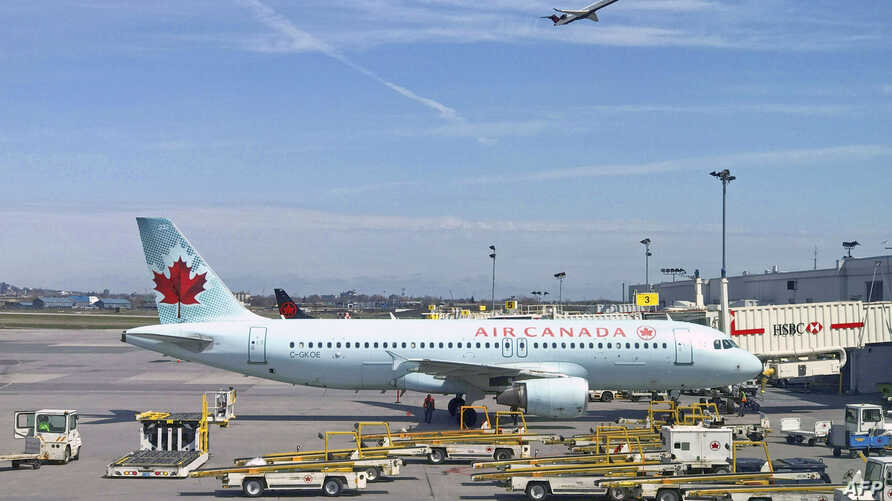 (FILES) In this file an Air Canada plane sits on the tarmac at Trudeau airport near Montreal, Canada. - Air Canada plans to…
