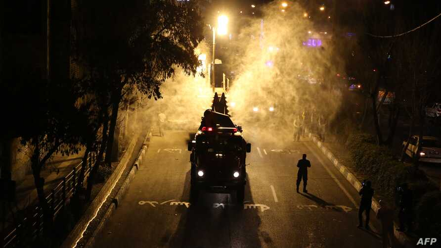 TOPSHOT - Iranian firefighters disinfect streets and alleys in southern Tehran to halt the wild spread of coronavirus on March…