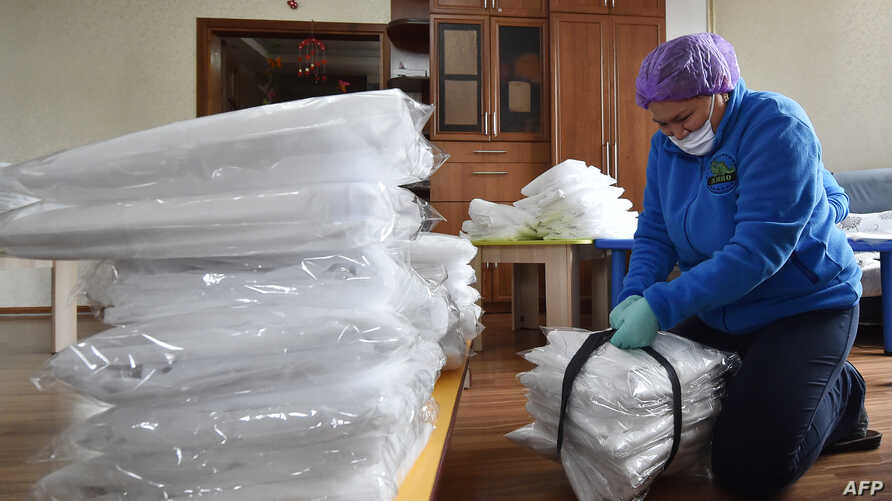 Civil activists wearing face masks and protective gloves pack protective suits before supplying to hospitals in Kyrgyzstan, in…