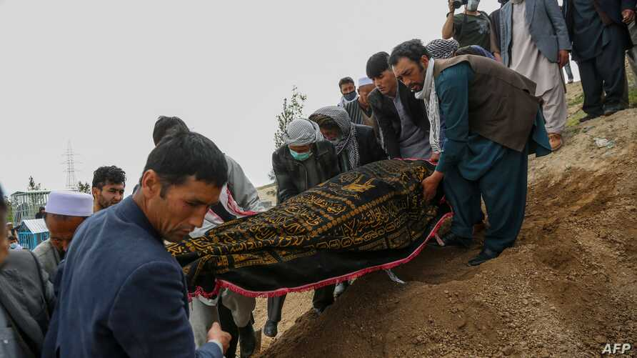 Mourners carry a covered dead body during a burial ceremony following a suicide attack in a maternity hospital, at a cemetery…
