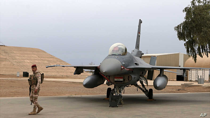 FILE - in this Tuesday, Feb. 13, 2018 file photo, an Iraqi army soldier stand guard near a U.S.- made Iraqi Air Force F-16 fighter jet at the Balad Air Base, Iraq.