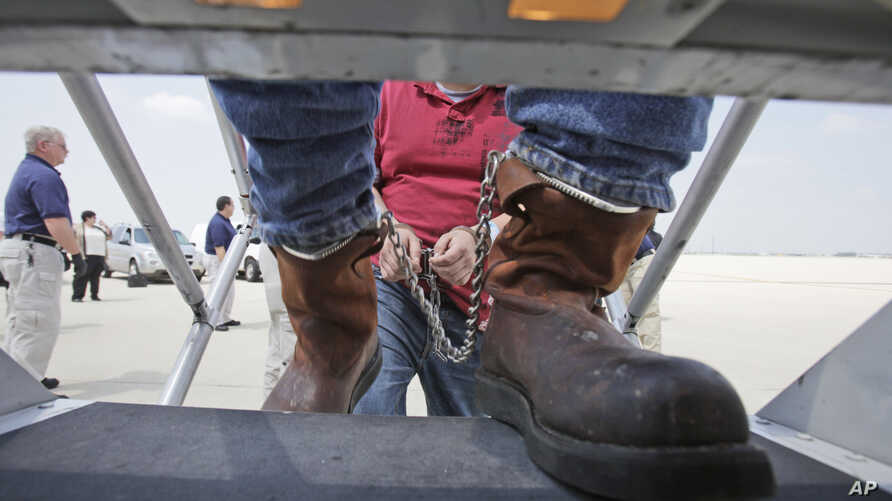 FILE - Shackled Mexican immigrants are boarded onto a U.S. Immigration and Customs Enforcement jet  chartered for deportation of illegal immigrants at O'Hare  in Chicago, Il.,May 25, 2010.