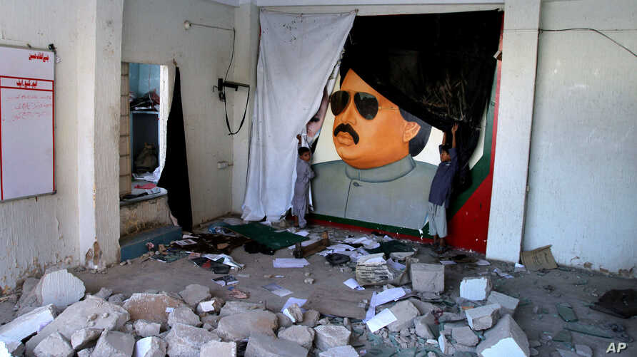 FILE - Pakistani children play next to the picture of Altaf Hussain, a top leader of Muttahida Qaumi Movement, or MQM, at one of his party offices demolished by authorities in Karachi Pakistan, Tuesday, Sept. 6, 2016.