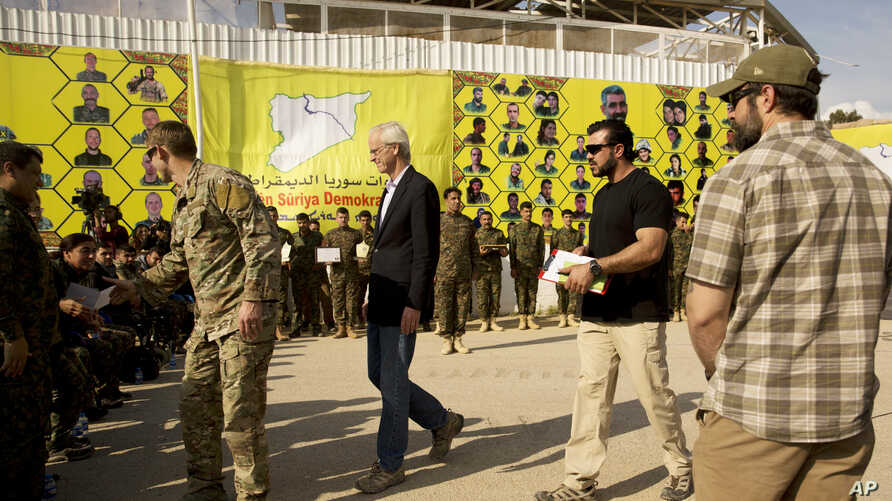 U.S. envoy William Roebuck, center, leaves the podium after speaking at a ceremony to celebrate U.S.-backed Syrian Democratic Forces defeat of Islamic State militants in Baghouz, at al-Omar Oil Field base, Syria, March 23, 2019