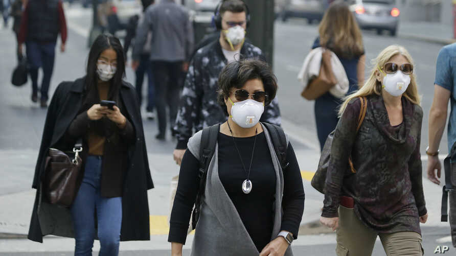 FILE - In this Nov. 9, 2018 file photo, people wear masks while walking through the Financial District in the smoke-filled air in San Francisco.