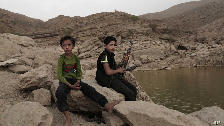 In this July 30, 2018, photo, a 17 year-old boy holds his weapon in High dam in Marib, Yemen.