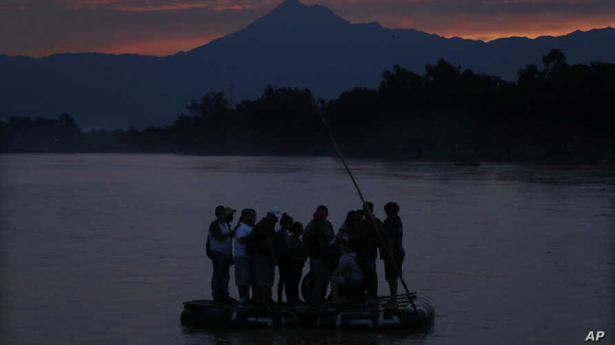 Central American migrants stand on a raft to cross the Suchiate River from Guatemala to Mexico, as the Tacana volcano stands tall near Ciudad Hidalgo, Mexico, early Monday, June 10, 2019. Mexican and U.S. officials reached an accord late Friday that…