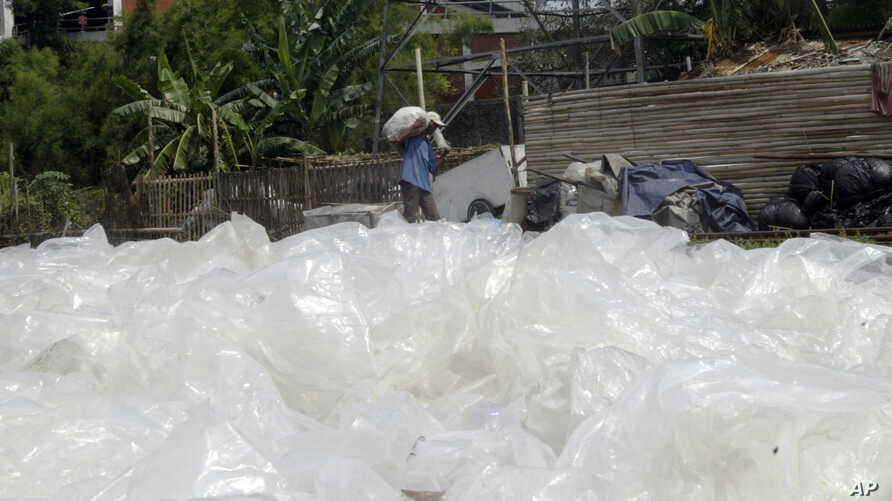 An Indonesian man carries used plastics to be sold to a recycling center, as he walks in front of discarded plastic bags, in Jakarta, Indonesia, Thursday, Dec 6, 2007. Delegates from 190 nations have assembled on the resort island of Bali, Indonesia…
