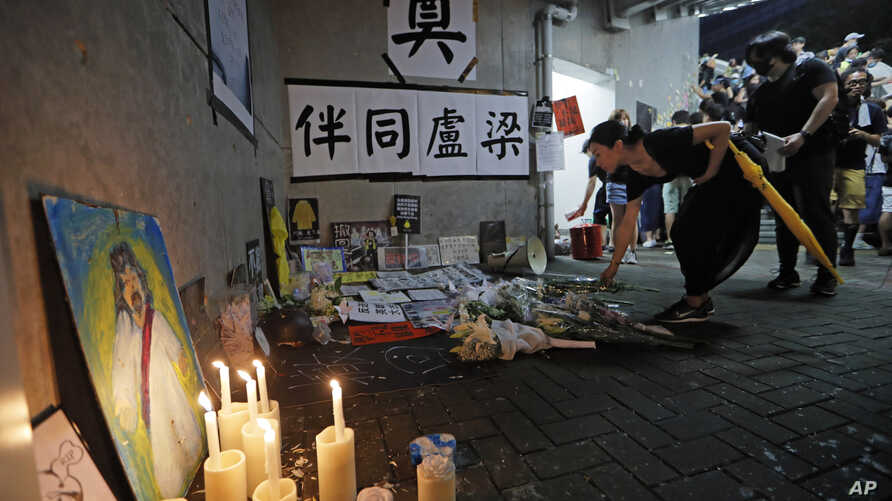 Mourners place flower tributes to a woman who supported the rally against the extradition law who jumped to her death a day earlier in Hong Kong, Sunday, June 30, 2019.
