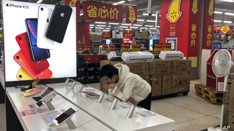 A man browses an iPhone unit on display at a section selling Apple's products together with Chinese made electric appliances at a hypermarket in Beijing, Thursday, May 9, 2019.