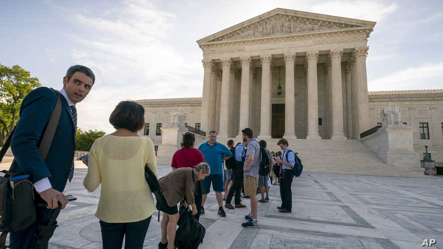 Visitors line up at the Supreme Court in Washington as the justices prepare to hand down decisions, June 17, 2019.