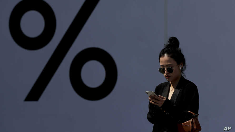 A Chinese woman wearing an Apple AirPods while browsing her iPhone past by a booth bearing a percent sign at the capital city's popular shopping mall in Beijing, Thursday, April 4, 2019. The U.S. and China opened a ninth round of talks on Wednesday,…