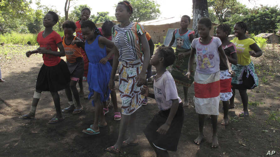 In this photo taken Friday, April 20, 2018 in the Gorongosa National Park, Mozambique, Mozambican girls dance as part of a girls' club program that aims to help girls stay in school longer and stay out of child marriage.