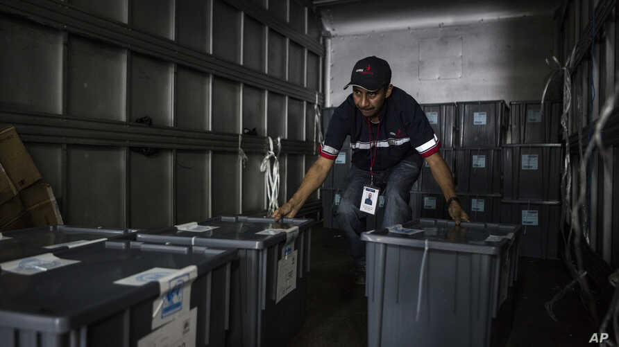A worker grabs boxes filled with ballots before being distributed to polling stations in Guatemala City, June 15, 2019.