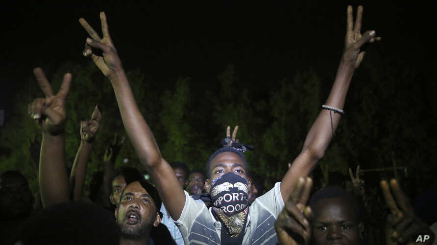 Sudanese protesters flash victory signs and shout slogans against the military council, as they gather during a sit-in, in Khartoum, Sudan, in Khartoum, June 20, 2019.