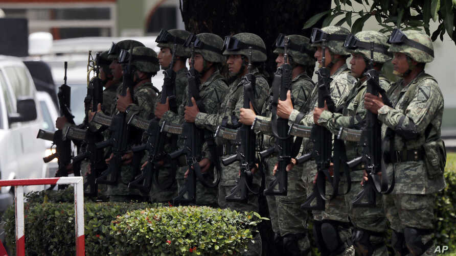 Mexican soldiers present arms as the country's Minister of Defense drives by, in Tapachula, Mexico,  June 11, 2019.