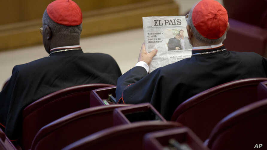 Spanish Cardinal Ricardo Blazquez Perez, right, reads a newspaper showing a picture of gay bishop Krzysztof Charamsa and his partner Eduard before the start of the morning session of the Synod of bishops on family issues, at the Vatican, Friday, Oct…