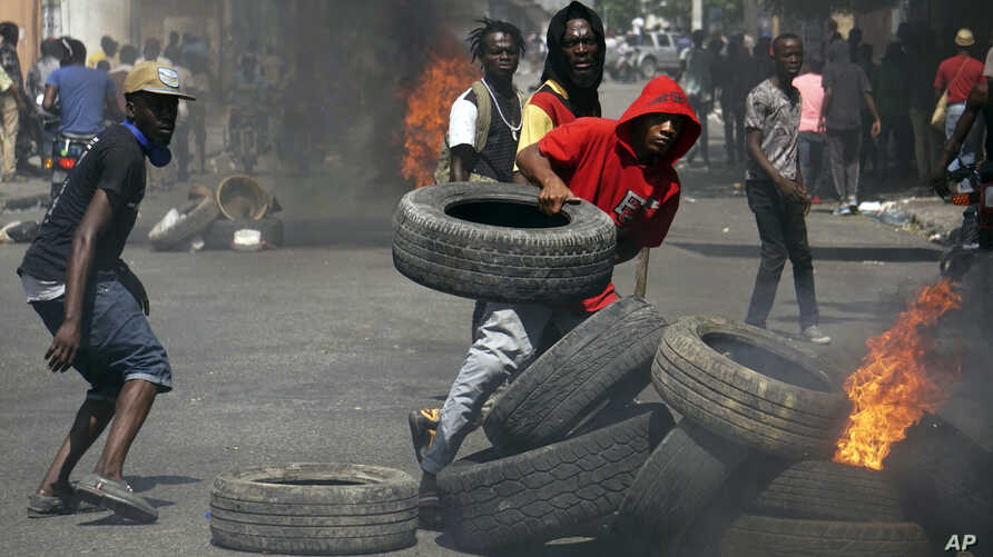 Anti-government protesters set up a barricade of burning tires as they demand the resignation of President Jovenel Moise in Port-au-Prince, Haiti, Thursday, June 13, 2019. Thousands of protesters demanding the resignation of President Jovenel Moïse…