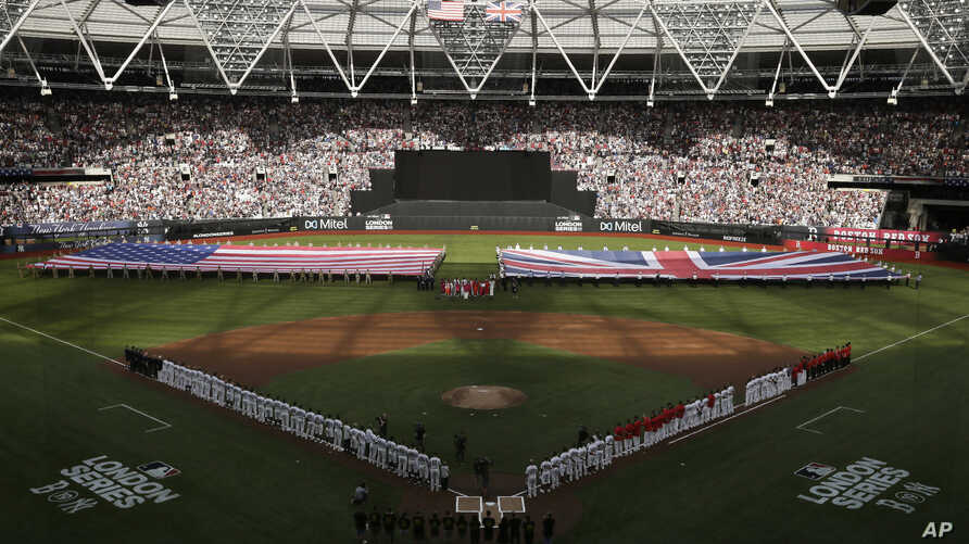 Boston Red Sox and New York Yankees players line up as flags are unfurled before a baseball game, Saturday, June 29, 2019, in London. Major League Baseball made its European debut game Saturday at London Stadium. (AP Photo/Tim Ireland)