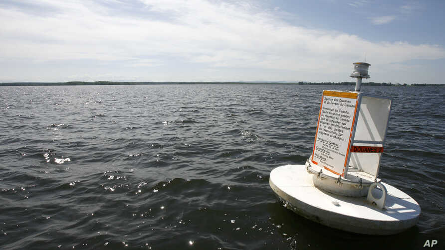 FILE - A floating marker indicates the border between the U.S. and Canada on Lake Champlain, in Vermont, June 25, 2008.