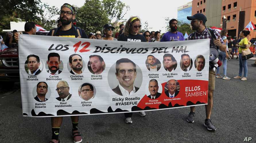 """Protesters hold a banner featuring resigned Gov. Ricardo Rosselló, center, amid other politicians that reads """"The 12 disciples of evil. Them too."""" as they demand the resignation of Justice Secretary Wanda Vazquez in San Juan, Puerto Rico, July 29, 2019."""