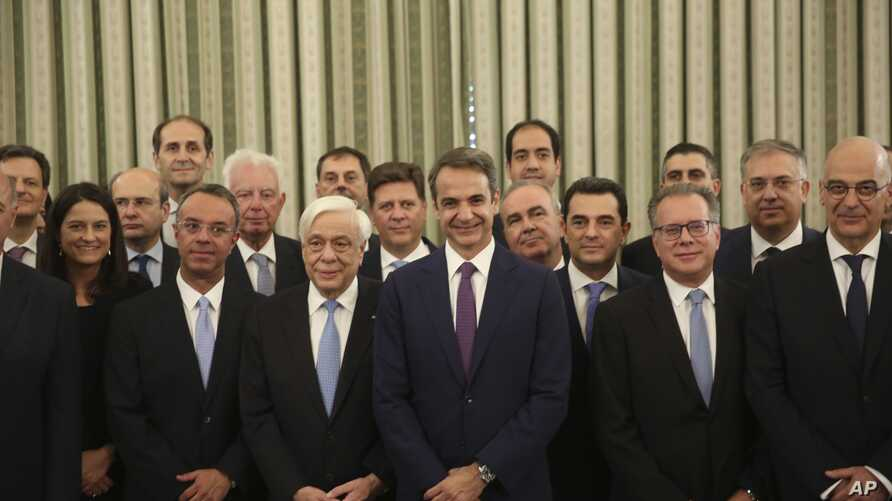 Greece's new cabinet pose for the photographers during the swearing in ceremony at the Presidential palace in Athens, Tuesday, July 9, 2019. Cabinet has been sworn in, two days after conservative party leader Kyriakos Mitsotakis won early elections…