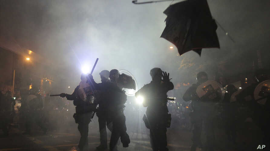 A broken umbrella sails near riot police during a confrontation with protesters in Hong Kong, July 21, 2019.