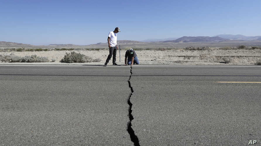 Ron Mikulaco, right, and his nephew, Brad Fernandez, examine a crack caused by an earthquake on State Route 178, July 6, 2019, outside of Ridgecrest, Calif.