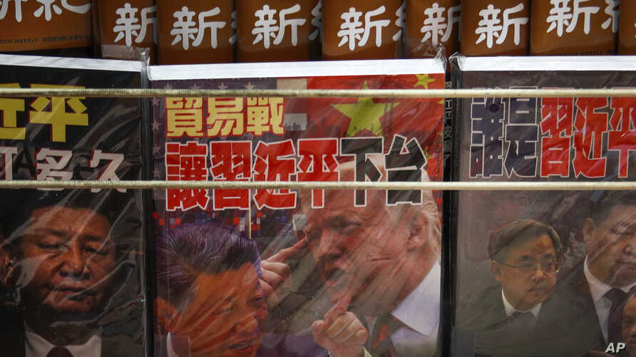 Magazines featuring Chinese President Xi Jinping and U.S. President Donald Trump on trade war are on sale at a roadside bookstand in Hong Kong, July 4, 2019.