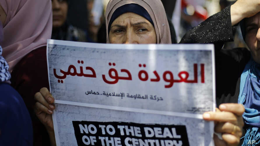 """A Palestinian woman holds a placard with Arabic that reads: """"The return is a definite right"""" during a demonstration organized by the Islamic militant group Hamas against a U.S.-sponsored Middle East economic workshop in Bahrain, in front of the…"""