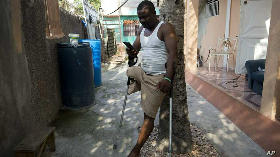In this June 5, 2019 photo, amputee and prosthetic technician Wilfrid Macena leans against a tree in his yard as he looks at his smart phone, in Carrefour, Haiti. He recalled when he came to an institution run by Haiti's Episcopal Church in downtown…