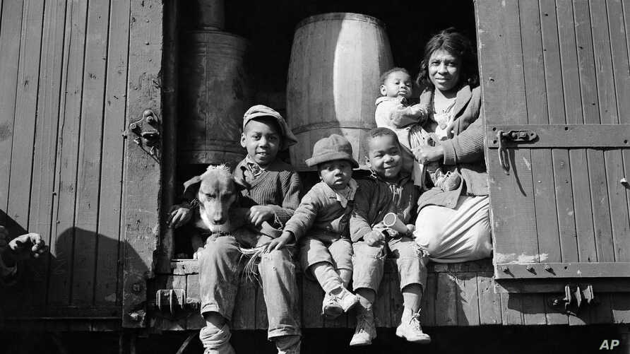 Driven from their home by the flood, this woman and her children have taken up residence in this box car in Elaine, Arkansas, Jan. 29, 1937. (AP Photo)