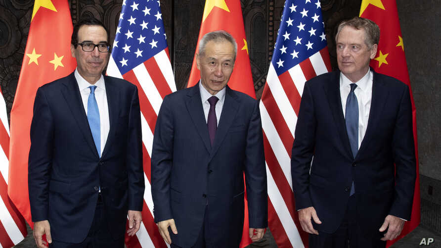 Chinese Vice Premier Liu He, center, poses with U.S. Trade Representative Robert Lighthizer, right, and Treasury Secretary Steven Mnuchin, for photos before holding talks at the Xijiao Conference Center in Shanghai Wednesday, July 31, 2019. (AP…