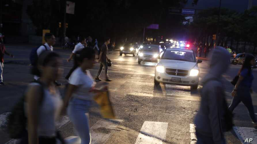 People cross a street during a blackout in Caracas, Venezuela, Monday, July 22, 2019. The lights went out across much of Venezuela Monday, reviving fears of the blackouts that plunged the country into chaos a few months ago as the government once…