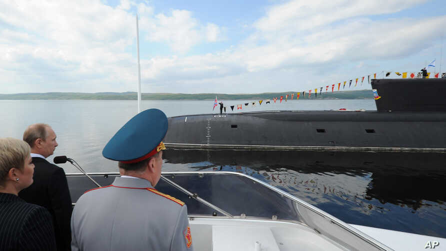 In this Sunday, July 27, 2014 photo Russian President Vladimir Putin, left, watches a nuclear submarine of the Northern Fleet to mark the country's Navy Day in Severomorsk, Russia.