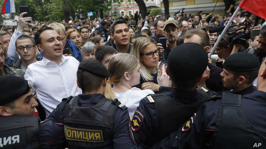 Russian opposition candidate and lawyer at the Foundation for Fighting Corruption Lyubov Sobol, center, and candidate Ivan Zhdanov, 2nd left, stand with other protesters in front of police line during a protest in Moscow, Russia, Sunday, July 14,…