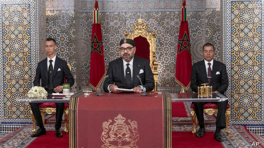 In this photo provided by the Moroccan News Agency (MAP), Morocco's King Mohammed VI, center, accompanied by his son Crown Prince Moulay Hassan, left, and brother Prince Moulay Rashid addresses the Nation in a speech aired on TV, at the Royal Palace…