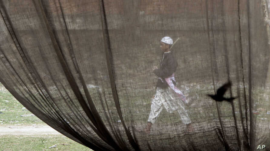 A Bangladeshi Muslim volunteer walks with a stick outside a jute tent as others work in preparation for the Islamic congregation on the banks of the Turag River in Tongi, 20 kilometers (13 miles) north of Dhaka, Bangladesh, Friday, Jan. 17, 2014…